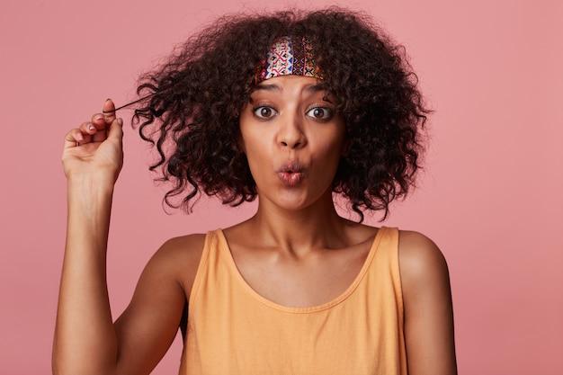 Ritratto di affascinante giovane donna bruna riccia con la pelle scura che guarda sorpreso e le labbra arricciate, giocando con i suoi capelli corti mentre si sta in piedi in abbigliamento casual