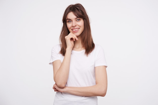 Portrait of charming young dark haired lady with natural makeup touching her face with raised hand and looking positively  with cheerful smile, standing against white wall