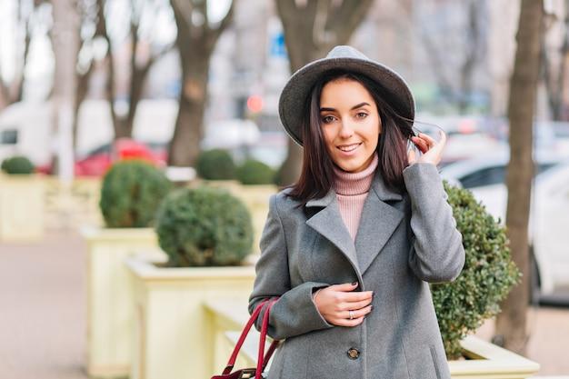 灰色の帽子で魅力的な若いおしゃれな女性の肖像画、都市公園の通りを歩いてコート。ブルネットの髪、笑顔、陽気な気分、エレガントな見通し。