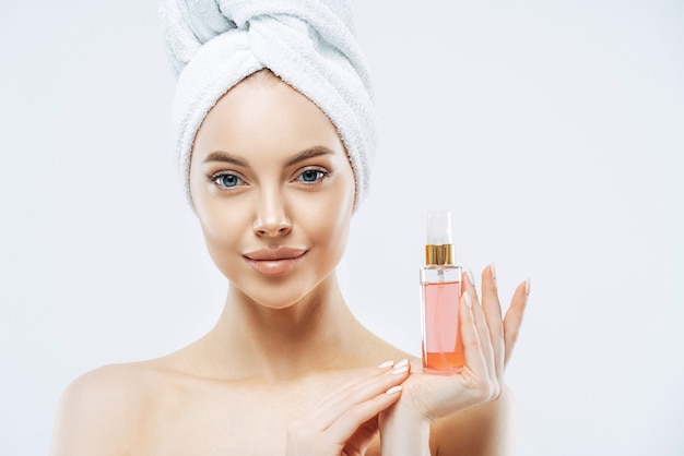 Portrait of charming young healthy woman holds bottle of expensive parfum, enjoys pleasant aroma, has healthy skin, wears bath towel on head, stands topless indoor. women and cosmetics concept
