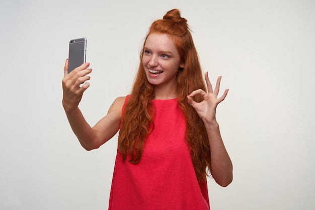 Portrait of charming young lady in pink dress wearing her foxy hair in bun, making photo of herselg with mobile phone, smiling widely to camera and rasing hand with ok gesture