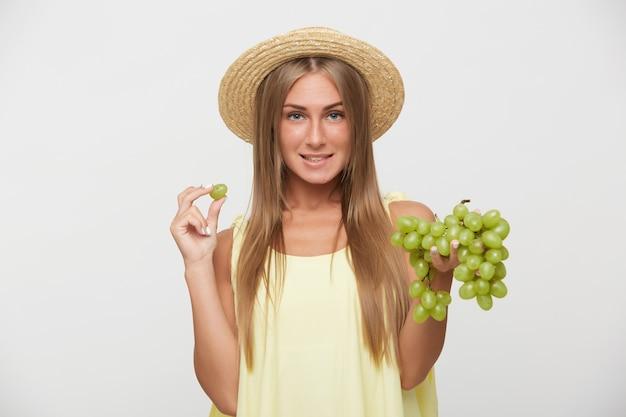 Ritratto di affascinante giovane dai capelli lunghi signora bionda con acconciatura casual che indossa cappello alle imbarcazioni mentre posa sfondo bianco, mordere underlip e tenendo grappolo d'uva