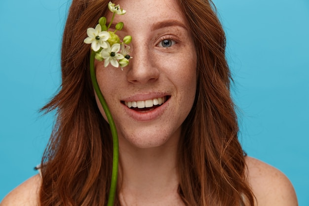 Portrait of charming young redhead female with wavy hairstyle keeping flowers on her face and smiling happily at camera, isolated over blue background