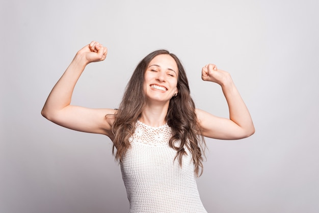Portrait of charming young woman celebrating success over white wall