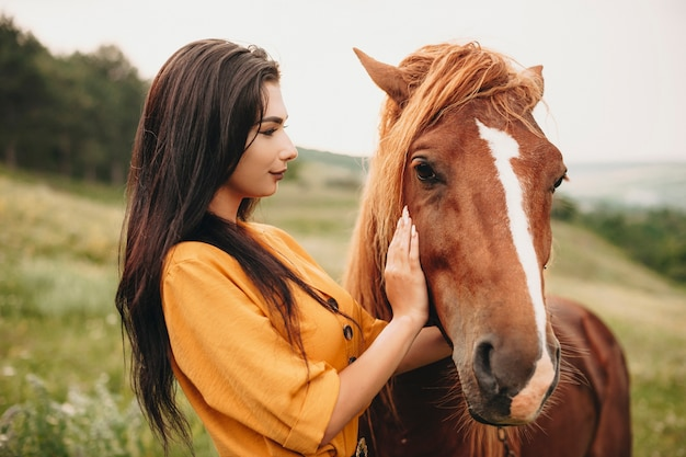 Portrait of a charming young woman embracing a horse. lovely female touching a horse face smiling.