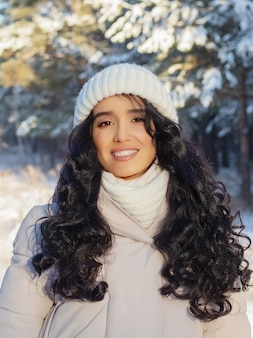 Portrait of charming young woman in fabulous winter forest