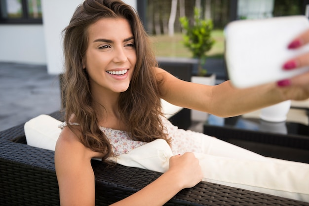 Portrait of charming young woman on terrace taking selfie photo with smartphone