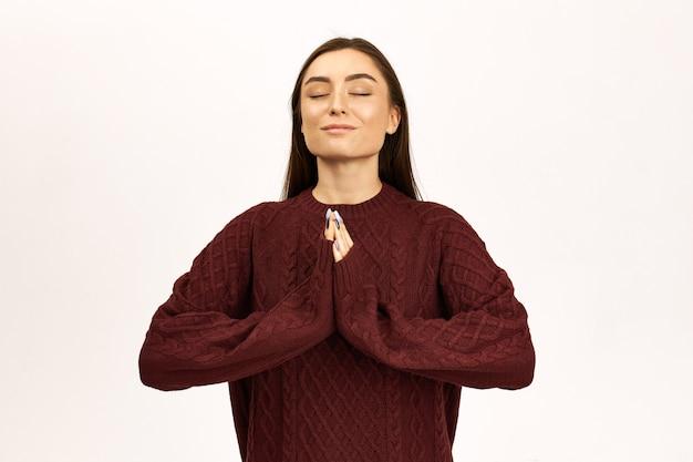 Ritratto di affascinante giovane donna con capelli lunghi scuri in posa in maglione gesticolando, premendo i palmi insieme, tenendo gli occhi chiusi, avendo calma pacifica espressione facciale, pregando, essendo grato