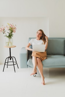 Portrait of charming young woman with laptop working at home while sitting on sofa