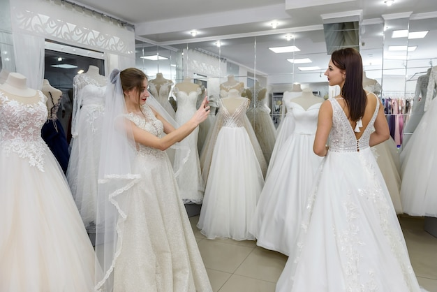 Portrait of charming young women wearing white gowns in bridal salon