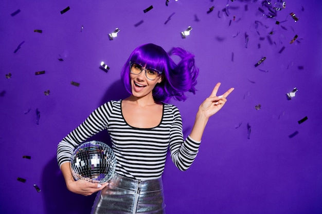 Portrait of charming youth with eyewear eyeglasses make v-signs hold disco ball scream dressed striped trendy shirt isolated over purple background