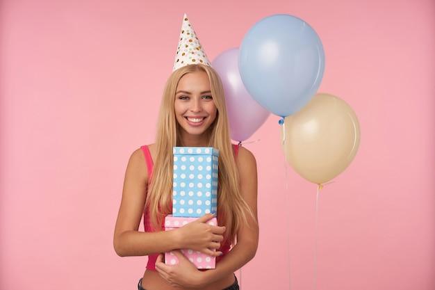 Ritratto di donna bionda positiva charmng con capelli lunghi che tiene scatole avvolte in regalo e mostra le sue piacevoli emozioni, in posa su sfondo rosa in abito da vacanza