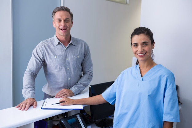 Portrait of cheeful doctor and man standing at desk