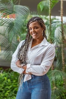 Portrait of a cheerful african american adult woman standing with her arms crossed and looking at the camera. adult woman with black and yellow braids posing on a background with plants and trees.