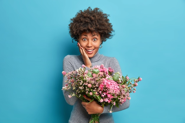 Portrait of cheerful african american woman accepts congratulations on birthday receives flowers has surprised expression