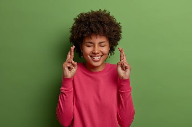Ritratto di donna afroamericana allegra attende il miracolo, prega e spera che i sogni diventino realtà, incrocia le dita per la buona fortuna, chiude gli occhi, sorride ampiamente, indossa un maglione rosa, isolato sul muro verde