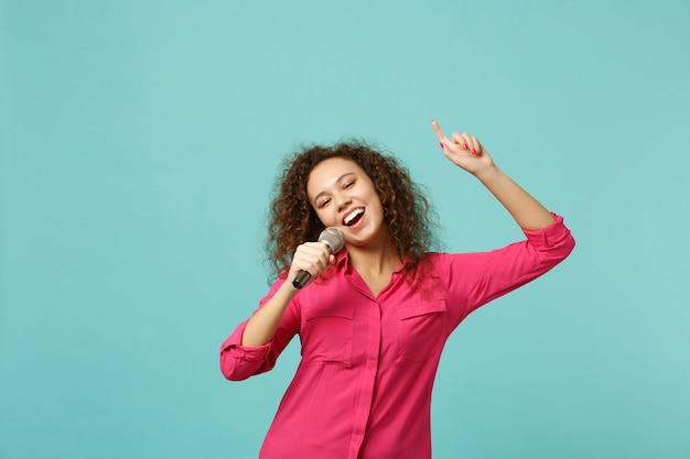 Portrait of cheerful african girl in casual clothes dancing sing song in microphone isolated on blue turquoise wall background in studio. people sincere emotions lifestyle concept. mock up copy space.