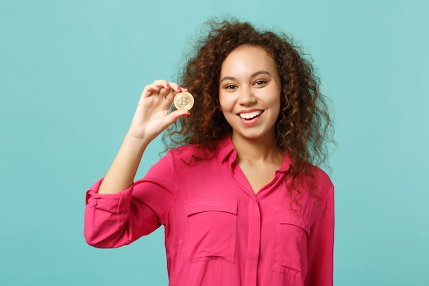 Portrait of cheerful african girl in casual clothes holding bitcoin future currency isolated on blue turquoise wall background in studio. people sincere emotions lifestyle concept. mock up copy space.