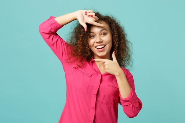 Ritratto di una ragazza africana allegra in abiti casual che fa gesto di cornice per foto con le mani isolato su sfondo turchese blu in studio. concetto di stile di vita di emozioni sincere della gente. mock up copia spazio.