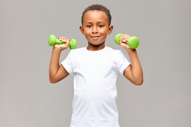 Portrait of cheerful afro american boy with skinny arms smiling happily while exercising in gym with two dumbbells, going to build strong healthy athletic body. fitness and children