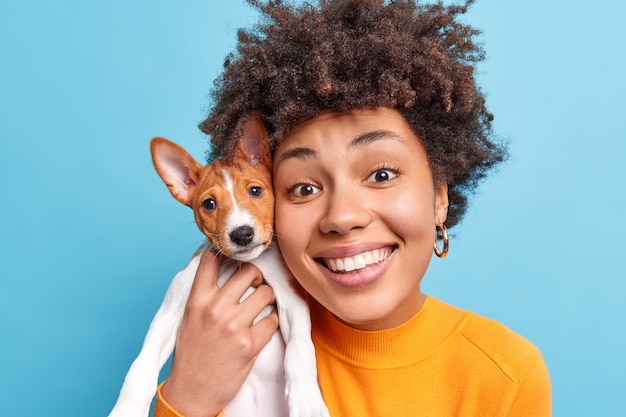 Portrait of cheerful afro american woman dog owner keeps small pedigree puppy closely to face happy to get pet as present has new friends looks happily  isolated over blue wall