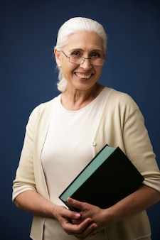 Portrait of cheerful aged woman in glasses, holding book