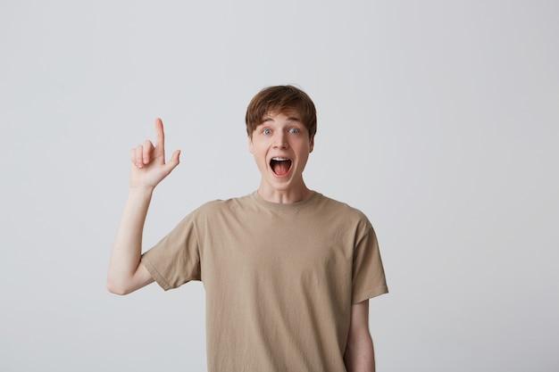 Ritratto di allegro giovane stupito con le parentesi graffe sui denti e la bocca aperta indossa una maglietta beige si sente sorpreso e indica il copyspace isolato sopra il muro bianco