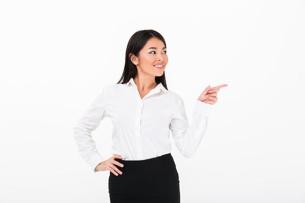 Ritratto di una donna di affari asiatica allegra che indica dito