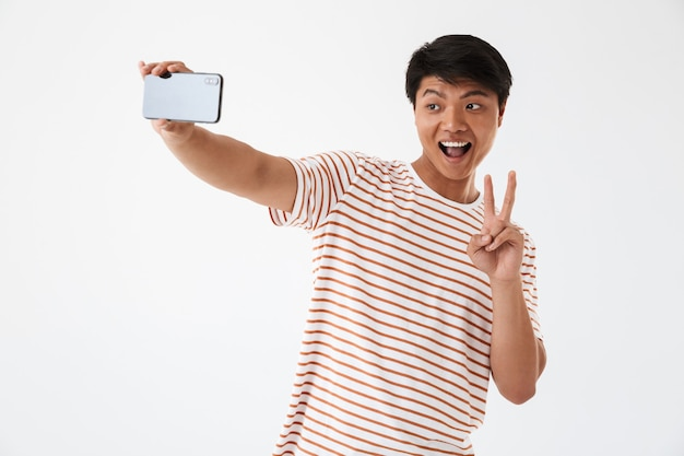 Portrait of a cheerful asian man showing peace gesture