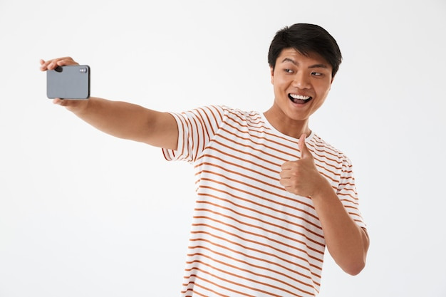 Portrait of a cheerful asian man showing thumbs up