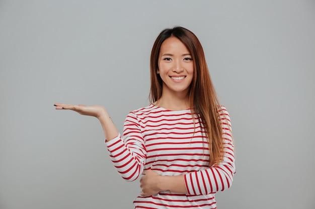 Portrait of cheerful asian woman holding copy space