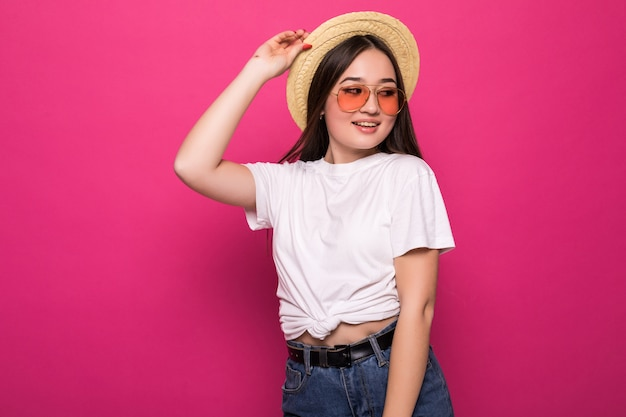 Portrait of a cheerful asian woman over pink wall.