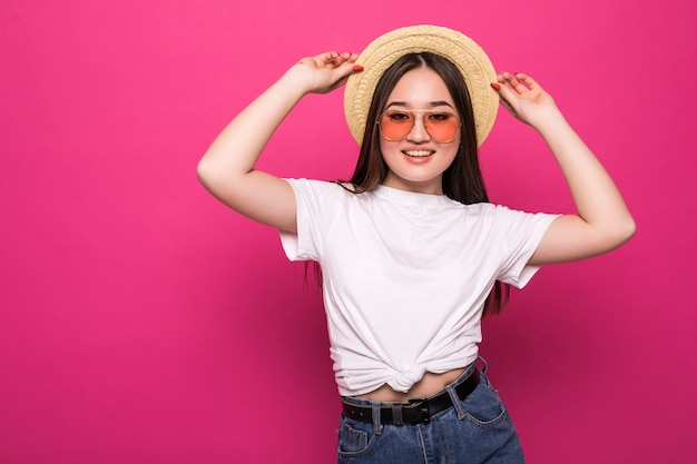 Portrait of a cheerful asian woman over pink wall