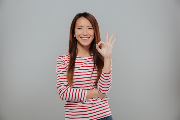Portrait of a cheerful asian woman showing ok gesture