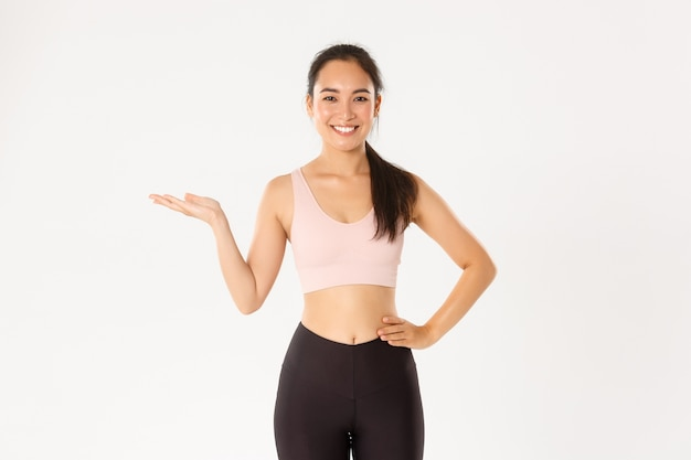 Portrait of cheerful attractive asian fitness coach, female athlete introduce or demonstrate product for workout, holding something on hand.