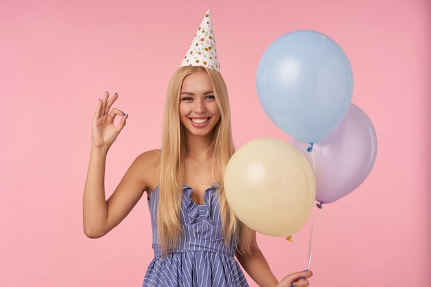 Portrait of cheerful attractive blonde female raising hand with ok gesture while standing over pink background with multicolored air balloons, looking at camera happily and smiling broadly