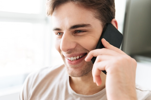 Portrait of cheerful attractive man talking on phone at home