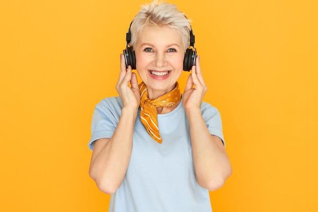 Ritratto di donna di mezza età attraente allegra con i capelli corti tinti che ascolta le canzoni usando le cuffie senza fili, avendo un'espressione facciale gioiosa.