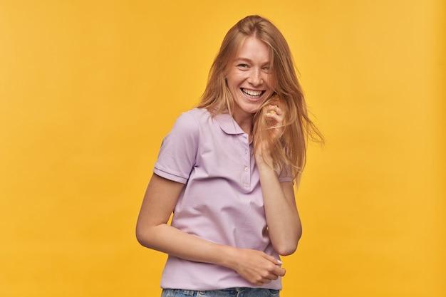 Ritratto di donna attraente allegra con le lentiggini in maglietta lavanda sorridendo e guardando la telecamera su giallo
