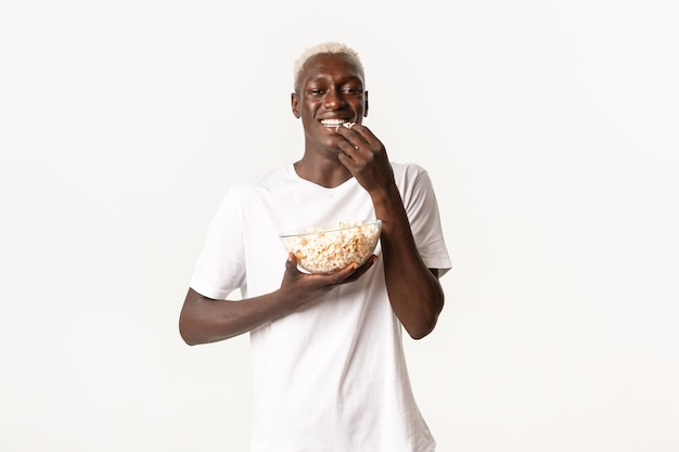Portrait of cheerful attractive young african-american guy enjoying watching movie and eating popcorn, looking at tv over white background.