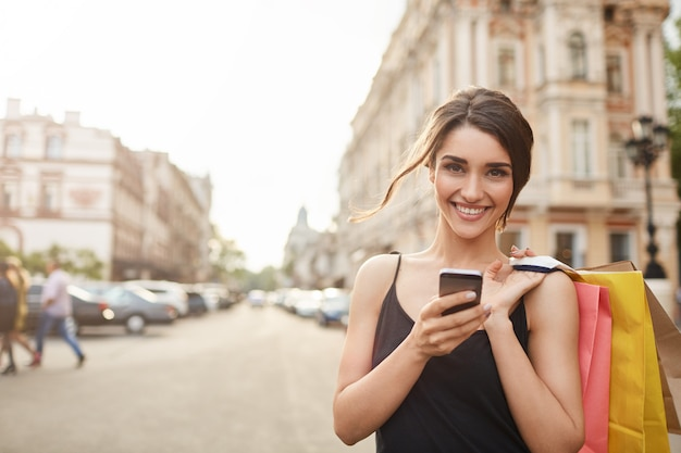 Portrait of cheerful attractive young caucasian woman with dark hair in black dress smiling in camera with teeth, holding shopping bags and smartphone in hands, catting with friend. soft focus