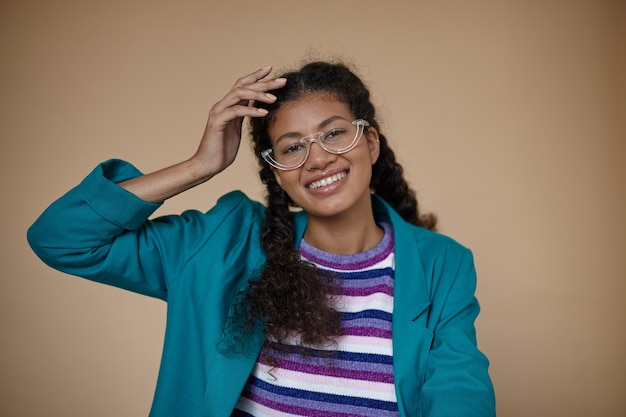 Portrait of cheerful attractive young curly brunette lady with dark skin wearing eyewear while posing, keeping hand on her head and smiling happily