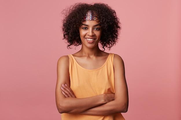 Ritratto di allegra attraente giovane signora dalla pelle scura con capelli castani ricci corti che guarda positivamente con un sorriso piacevole, piegando le mani sul petto mentre è in piedi