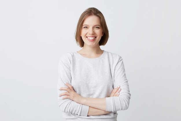 Portrait of cheerful attractive young woman in longsleeve standing with arms crossed and smiling