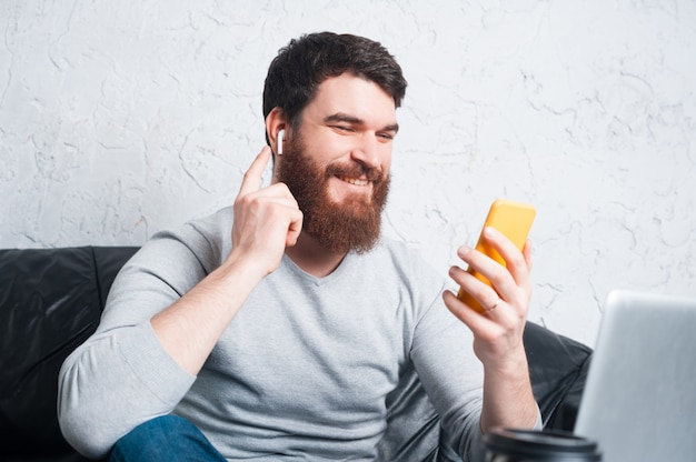 Portrait of cheerful bearded man in casual tallking with someone and touching airpods