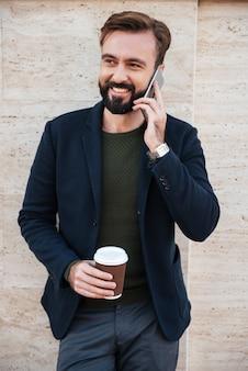 Ritratto di un uomo barbuto allegro che tiene la tazza di caffè