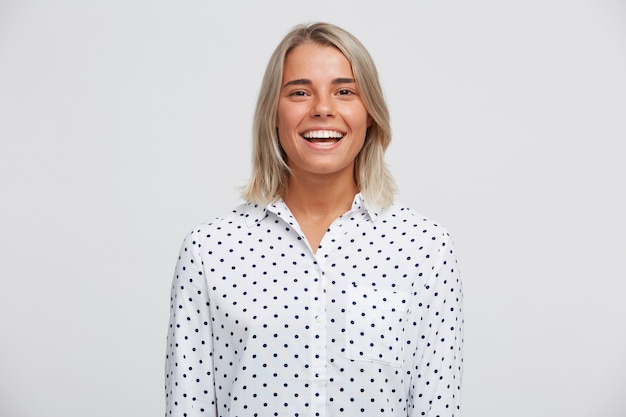 Portrait of cheerful beautiful blonde young woman wears polka dot shirt feels happy, standing and smiling isolated over white wall