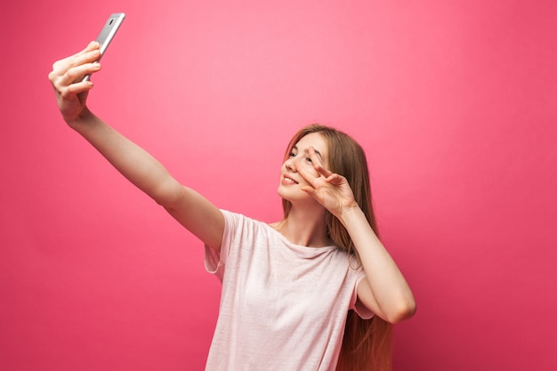 Portrait of cheerful beautiful girl, photographed, taking selfie