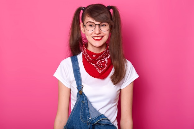Portrait of cheerful beautiful girl with long pigtails, wears t shirt, denim overalls and red bandana on neck