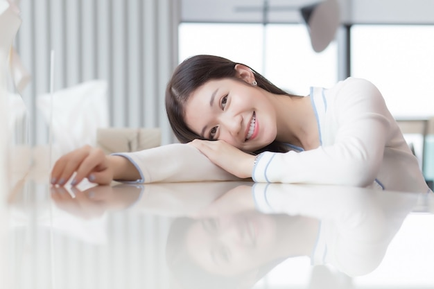 Portrait of cheerful beautiful young female is feeling happy and smile  laying on desk. woman model sit in the glassed room as business room.
